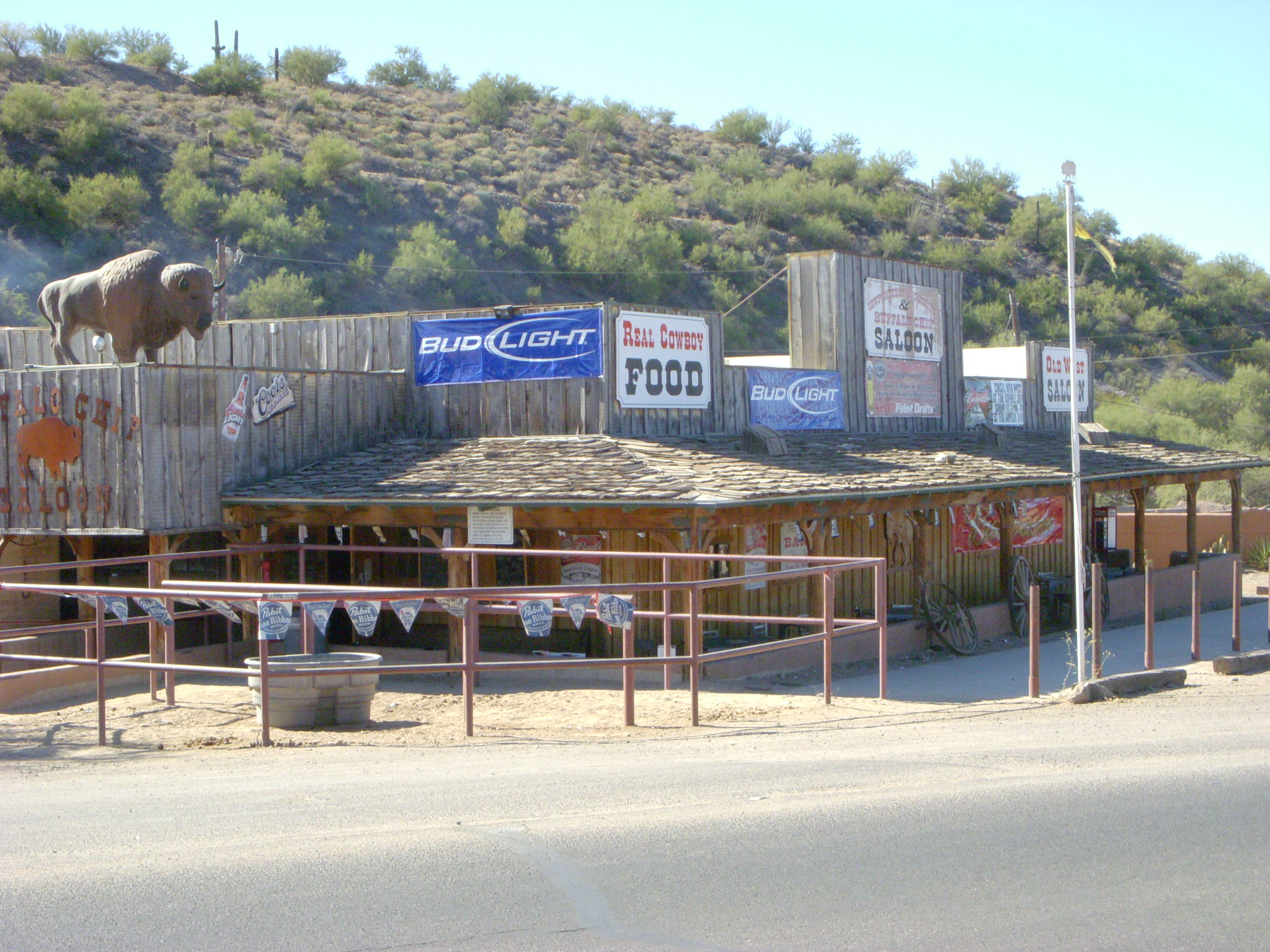 An outside view of the Buffalo Chip Saloon with horse stables in front and a large buffalo statue on a raised platform.