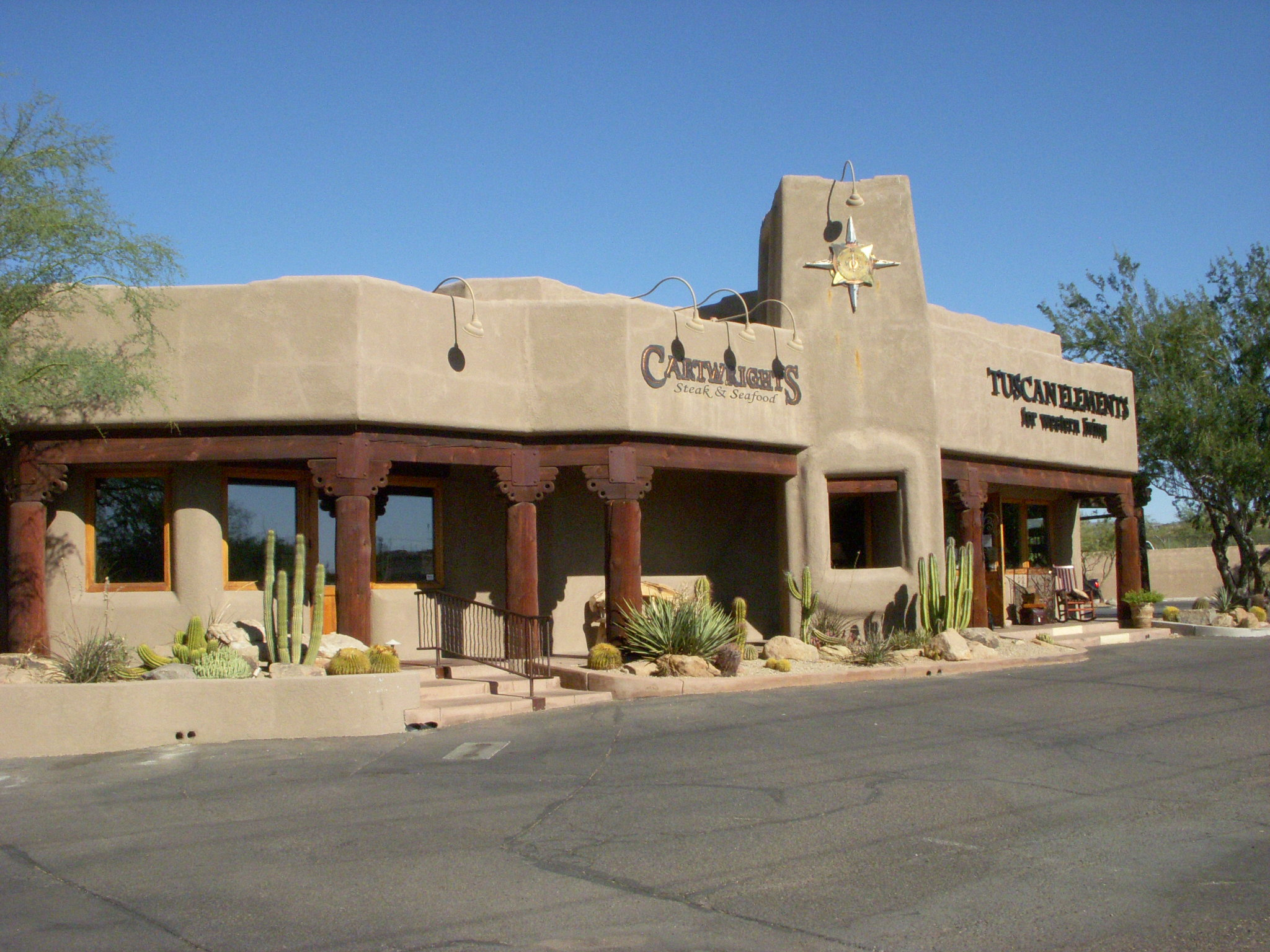An outside view of Cartwright's Restaurant's beige Spanish-style building with cacti in front.